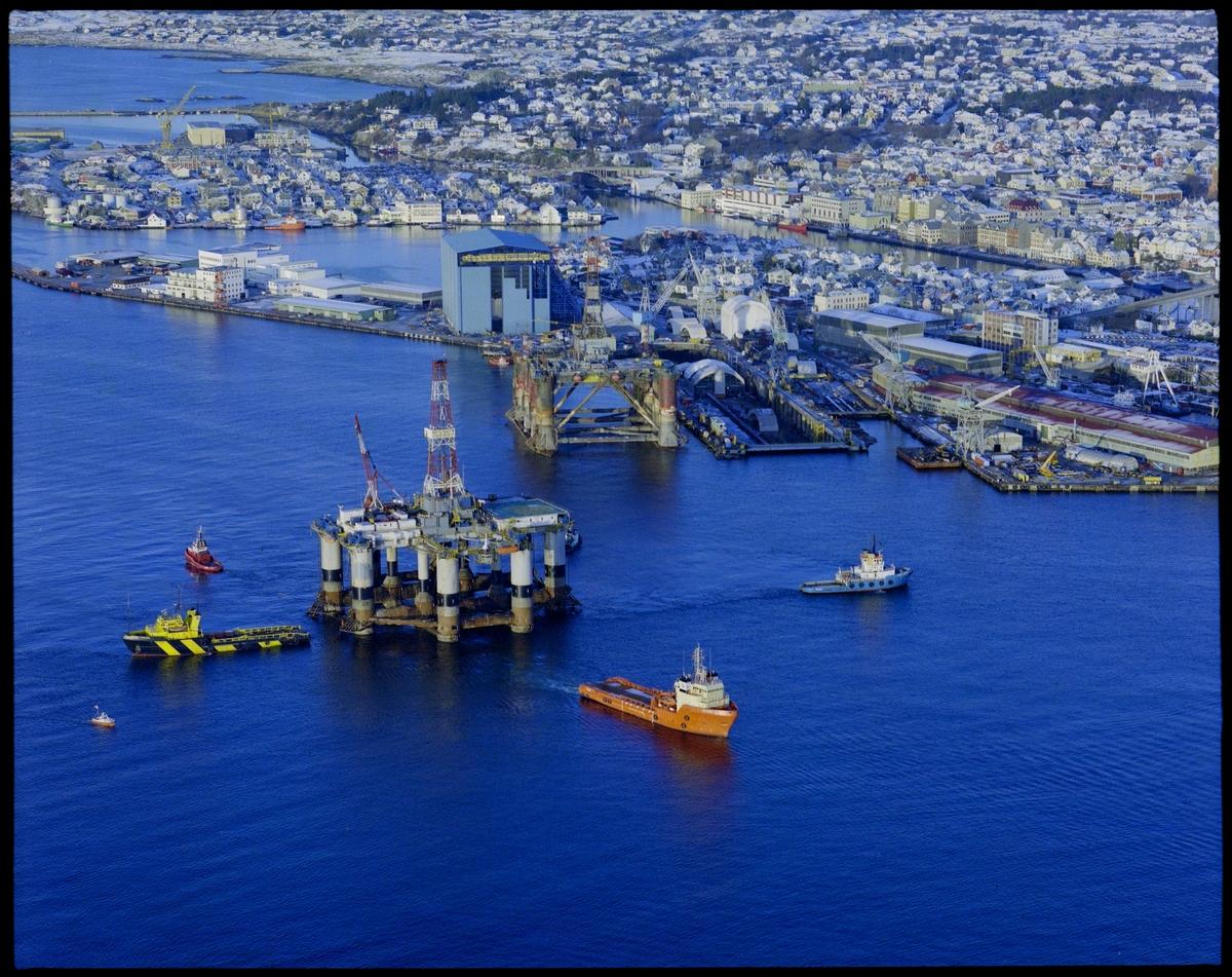 """Flyfoto av 3 skip som arbeider med fortøying av en borerigg utenfor Haugesund Mekaniske Verksted. Den store, blå """"Nordsjøhallen"""" er nesten ferdig bygget."""