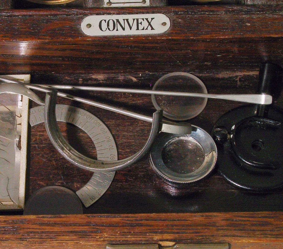"""Etuiet er sinket sammen i hjørnene, fast """"innredning"""" for brilleglass m.m. er trolig limt fast. Skrudde hengsler for lokk. Etuiets lokk er polstret innvendig.  Euiet inneholder: 15 par konkave utskiftbare brilleglass, 15 par konvekse utskiftbare brilleglass, 13 prismeglass (opprinnelig 15?), 6 stk fargede brilleglass, 5 stk. sorte skiver (m.spalte, små hull m.m.) 1 stk. brille m. plass til utskiftbare brilleglass m.m. 1 stk. speilglass, m.m."""