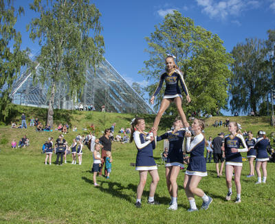 Cheerleaderjenter danner pyramide, Hamardomen i bakgrunnen.