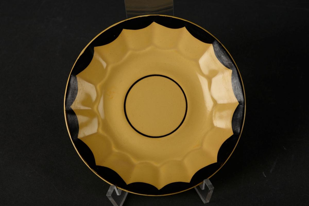 Gult tefat med en svart sirkel i midten, og et svart mønster rundt kanten.