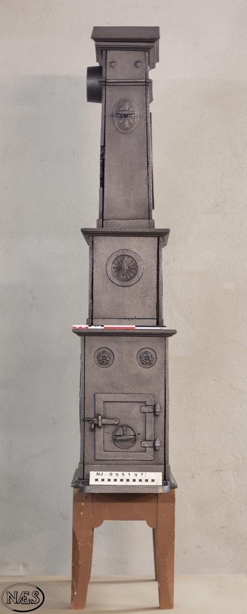Ovn i to etasjer med obeliskform på toppen. Avsluttes med en gavl. På ovnens langside 1.etg - Frukt og blomstervase i liggende oval. Ovnsdør på kortside og innskrift på motsatt kortside. Langside 2.etg har en rundbuet åpning med en rosett i hvert øvre hjørne. Stor rosett på kortside. Obeliskformen har et stående ovalt gittervindu på langsiden. Ventiler i 2. og 3. etg.