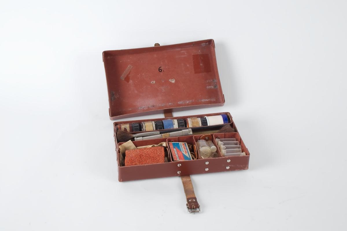 Pensler, pulver og utstyr for fingeravtrykksundersøkelser pakket i en brun koffert.