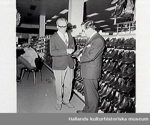 """Bilder i samband med tidningsartikeln """"Nya Domusvaruhuset klart efter om- och tillbyggnad"""", publicerad i Hallands Nyheter, 1970-06-15.  Bild G8284: Disponent Eric Engdahl och Bertil Emanuelsson står vid en skohylla. Bild G8285: Vy längs stråk utmed hyllgavlar."""