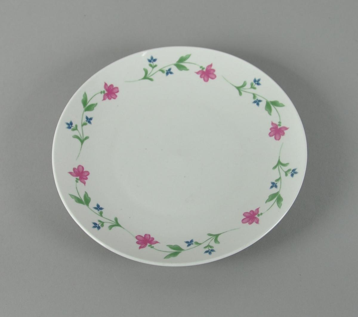 Hvit frokosttallerken av glassert keramikk, med blomsterbord av røde og blå blomster rundt kanten.