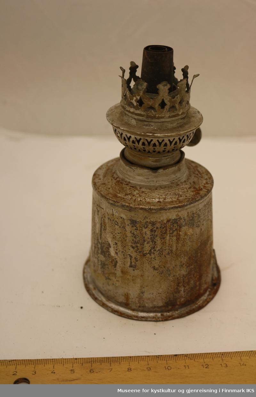 En parafinlampe med vekebrenner. Parafinbeholderen er tilsynelatende hjemmelagd, og består av forskjellige plater og andre deler loddet sammen. Brenneren har feste for en tynn lampeskjerm i glass, men denne mangler.