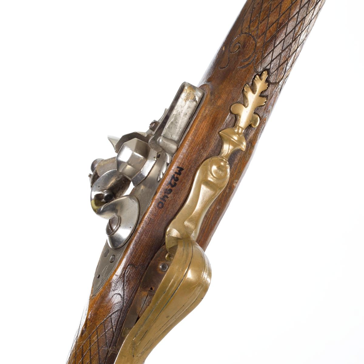 Flintlåsgevär försedd med rund pipa och åttakantigt kammarstycke. Geväret har hel stock med bakplåt i stål som går upp över kolvryggen. Kolvens ena sida har ett skuret motiv föreställande en älg. Den andra har en enklare bladranka. Kolvhalsen är rutad, varbygeln är i utdragen form och tillverkad av gjuten och bearbetad mässing. Låset har en kraftig S-formad hane som är förnicklad, och fängpannelockets fjäder ligger utanpå låsblecket. Laddstocksrännan har tre rörkor varav den mellersta har ett fäste för bärrem, och laddstocken är tillverkad av trä. Geväret är försett med ett gropsikte och mässingskorn. Pipan är slätborrad och har en innerdiameter på 17,5 m.m. Inskrivet i huvudkatalog 1974.