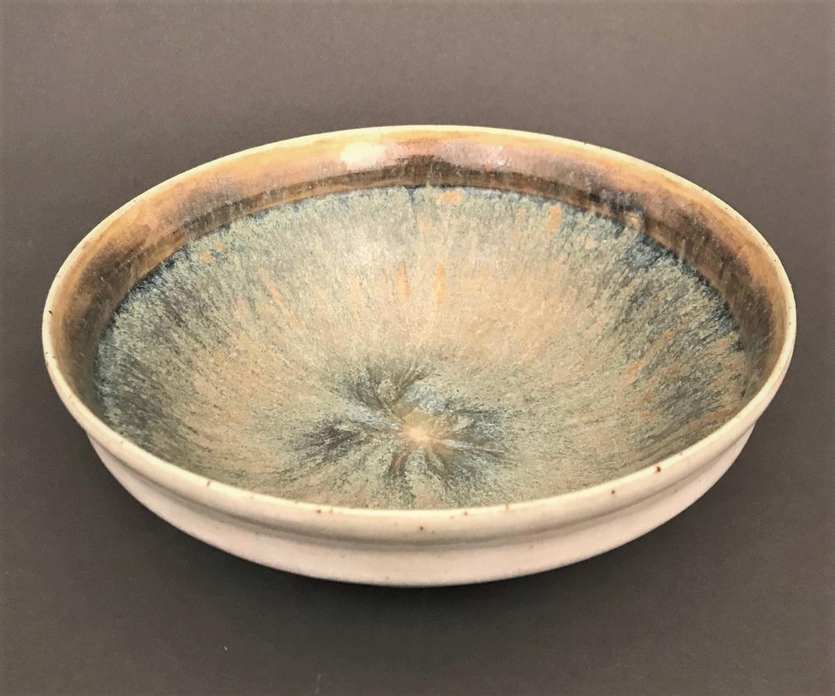 Sirkulær skål av steingods, som hviler på en lav sirkulær base. Yttersiden er dekket av gråfarget glasur, og dens øvre del er markert med en avrundet kant. Glasuren er krakelert på enkelte steder. Skålens monokrome ytre står i kontrast til dens polykrome indre. Langs innersiden av kanten kombineres okerfargede og mørkeblå fargetoner. Skålens bunn er blålig, og delvis dekket av en gråhvit flyteglasur med gulfargede innslag. Bunnen er stemplet «Auguste Delaherche / 3166».