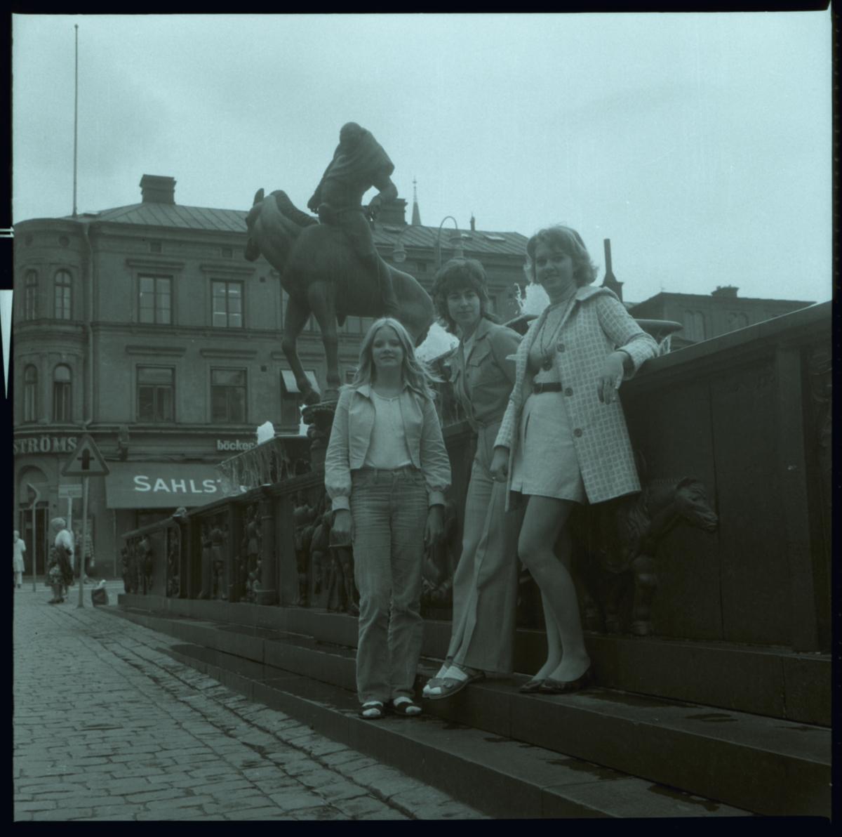 Stora torget sett västerut från Storgatan.Tre kvinnor står vid Folkungabrunnen, en skulptur av Carl Milles som invigdes 1927. Byggnaden i bakgrunden inrymmer Sahlströms bokhandel.