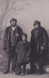 Två män och ett barn har ställt upp sig för studiefotografer