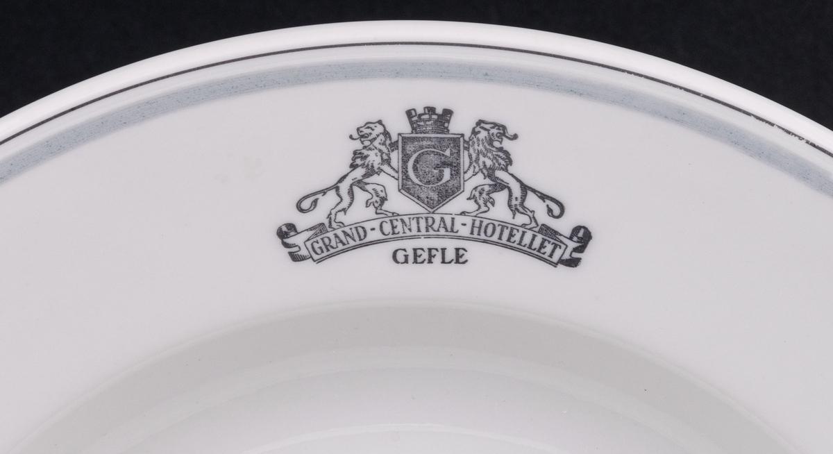 Tallrik,djup. Vit glasyr ljusgrå och mörkgrå dekor. På brättet emblemet Grand Central Hotellet Gefle, samt två lejon hållande Gefle vapen. Ytterst på brättet två tunna grå ränder.