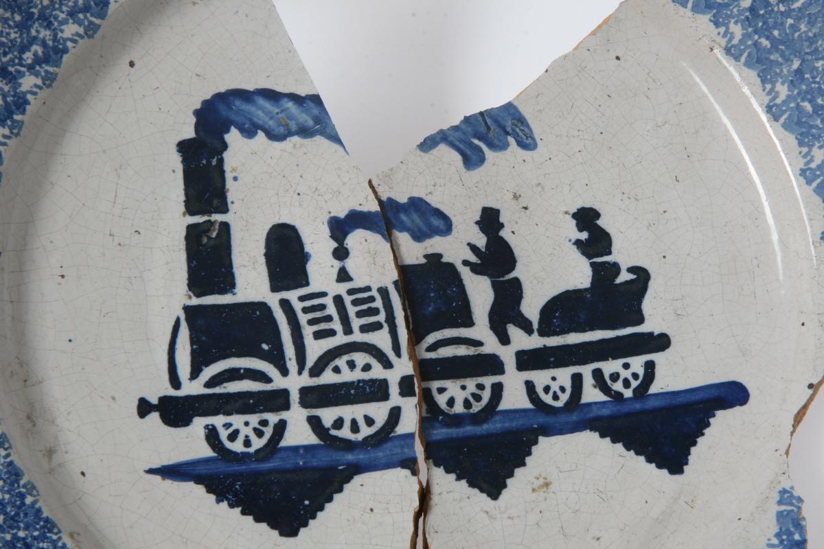 Fajanse, blå dekor: damplokomotiv med vogn. 2 deler, flere mangler.