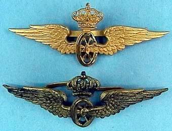 Tre mössmärken i form av krönta vinghjul av mässing, med vikben på baksidan.