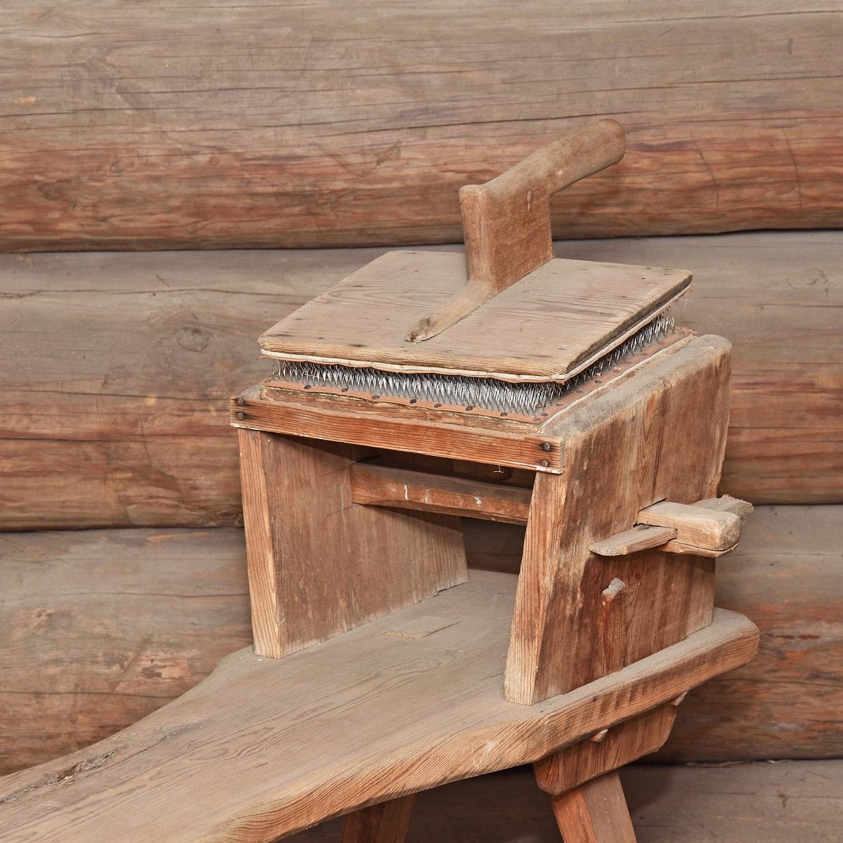 Kardbänk av furu, bestående av bänk (A), med kardstativ samt kardor (B) och (C) med metalldelar. Kardorna kan lossas från stativet.