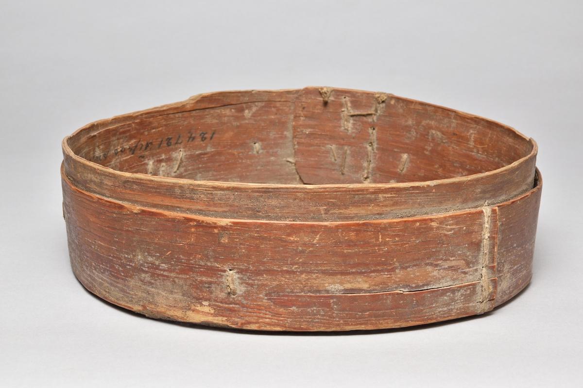 Mjölsikt av trä och tagelduk. Rund ram av dubbelt svept träspån som sytts samman med snöre. Siktduk vävd av svart och brunt tagel i ränder. Duken lagad med tygbitar på ett flertal ställen.