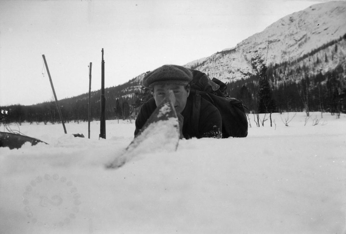 Karl Sannheim ligger i snøen med gevær i bakgrunnen. Et sirkulært merke med tallet 2 inni nederst  til venstre.