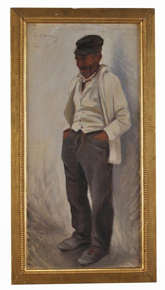"""Oljemålning, olja på duk, """"Man från Capri"""" av Erik Hedberg (1868-1959), enligt Accessionskatalog 1949. Man stående, sedd snett framifrån, grå byxor, vit väst och kavaj, uppknäppt, händerna i fickorna på byxornas framsida. Mörk skärmmössa. Ljusgrå bakgrund. (Enligt Kat.kort """"Studie från Capri)."""