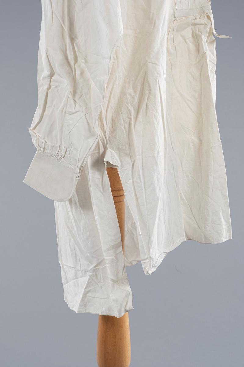 Smokingskjorte i bomull med stivet bryst og stivede mansjetter. Knepping av skjorten i front. En knapp i nakken, en i hver mansjett og tre knapper i brystet. I alt seks messingknapper trukket med stoff. Knappeøyene har messingkant. Det er stemplet inn initialer på snippen som ikke er mulig å tyde. Det er legg i skjortebrystet.