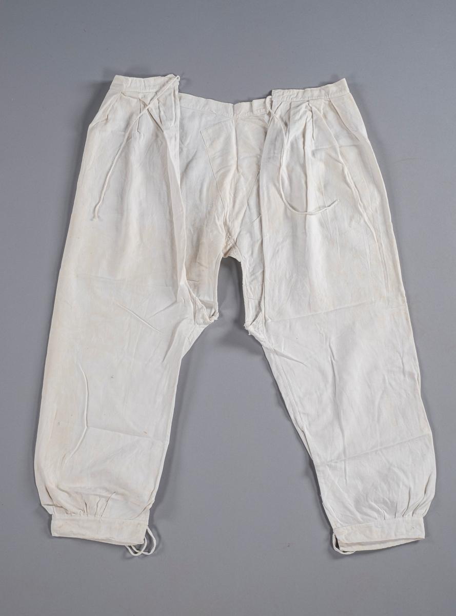 Underbukse i hvit bomull med åpning i skrittet. Den knytes igjen med flettet tråd i livet og ved knærne. Det er folder i front ved øvre kant og ved nedre kant på hvert bukseben. På baksiden av venstre bukseben er et hull lappet igjen. Buksen er forsterket i bakpartiet.