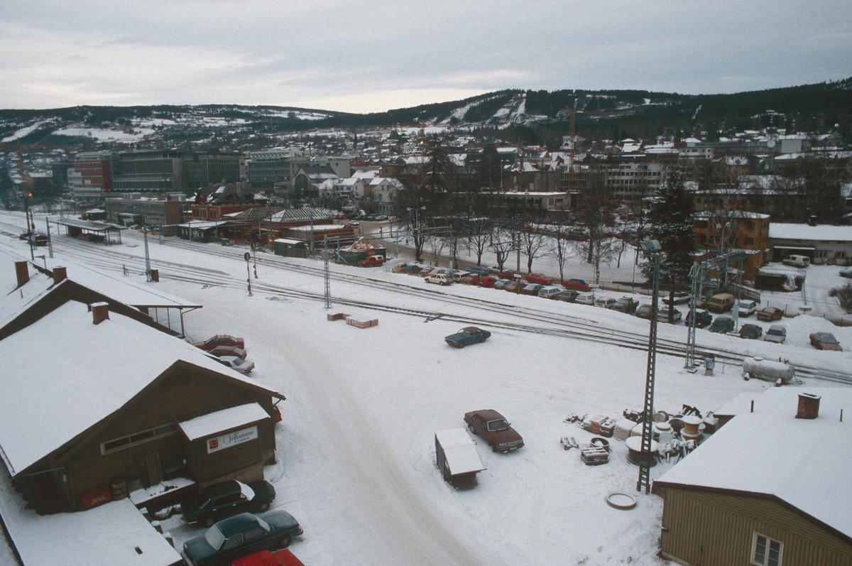 Lillehammer.  Jernbaneområdet før utbygging.  Bygningen i forgrunnen til venstre, godshuset, skal rives.  Lillehammer jerbanestasjon litt til venstre i bakgrunnen.  Utsikt mot nord fra kran over Mesnadalsvegen.