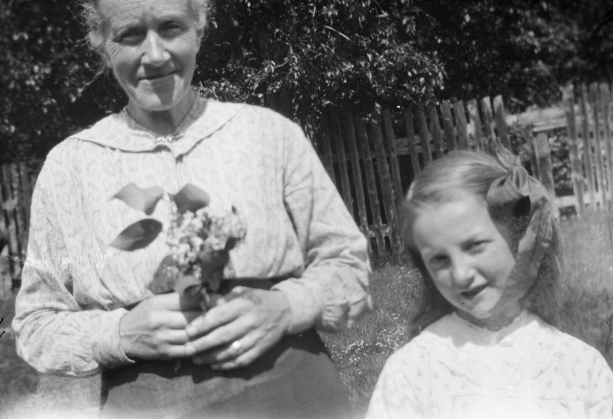 Eldre dame med blomsterbukett sammen med en jente.