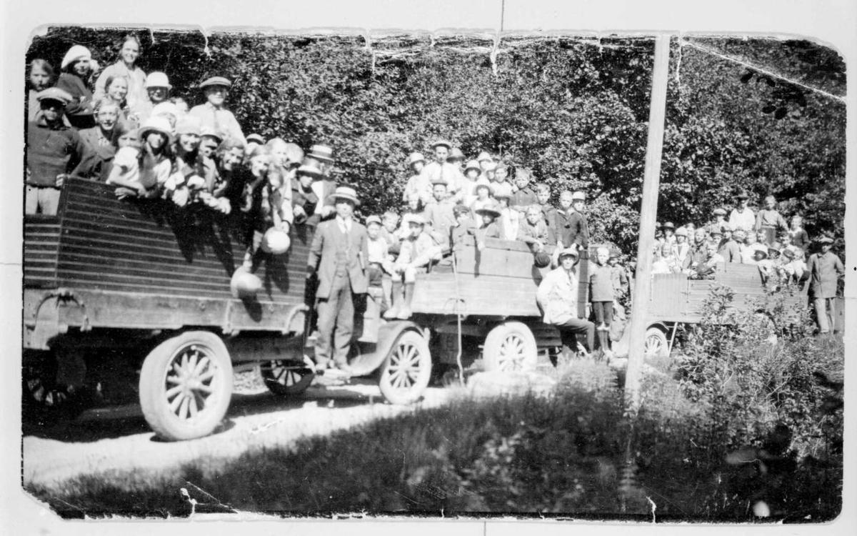 Repro: Tre lastebiler fulle med folk, store og små, på tur.