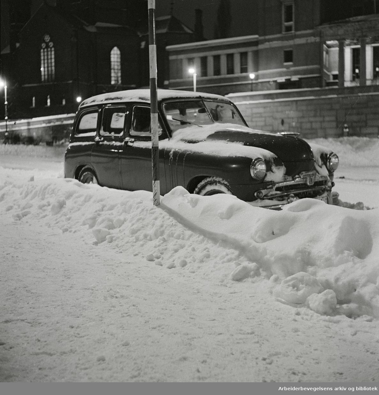 Parkert bil med snø på Arne Garborgs plass. Trefoldighetskirken og Deichmanske bibliotek i bakgrunnen. Desember 1959.