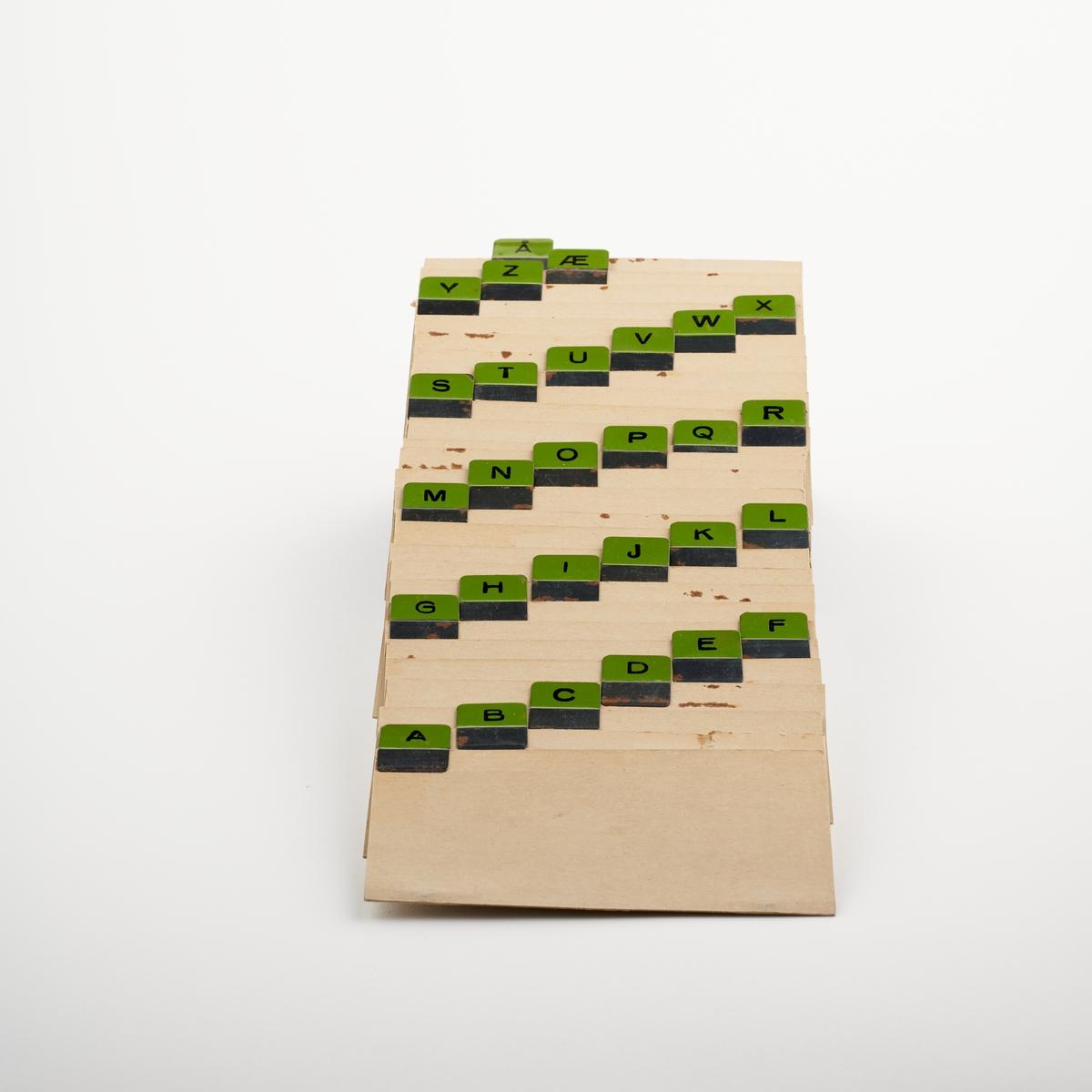 Skilleark i papir med bokstavene i alfabetet festet øverst i metall. Kortet med bokstaven ø mangler. Det er totalt 28 kort.  NAV-samlingen er en gruppe av gjenstander som har vært anvendt på sosialkontoret (Aetat - NAV) i Skedsmo kommune.