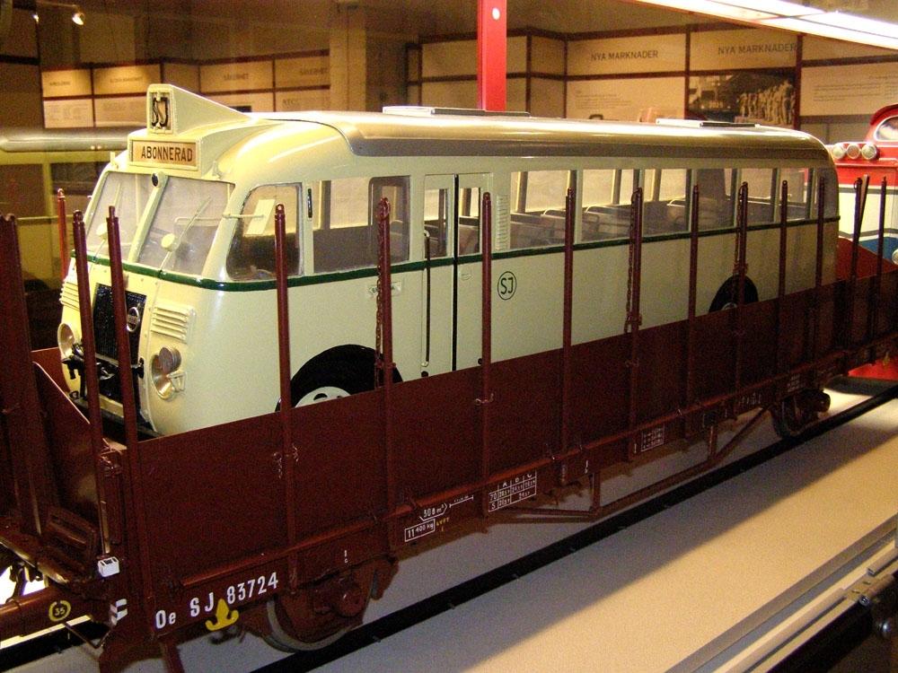 Modell av buss i skala 1:10. Bussen är gulmålad med grön rand, och SJ:s logga inom ring i grön färg. Grått tak. Detaljer i svart. Byggd för vänstertrafik Upplastad på vagn (Jvmf 12895).