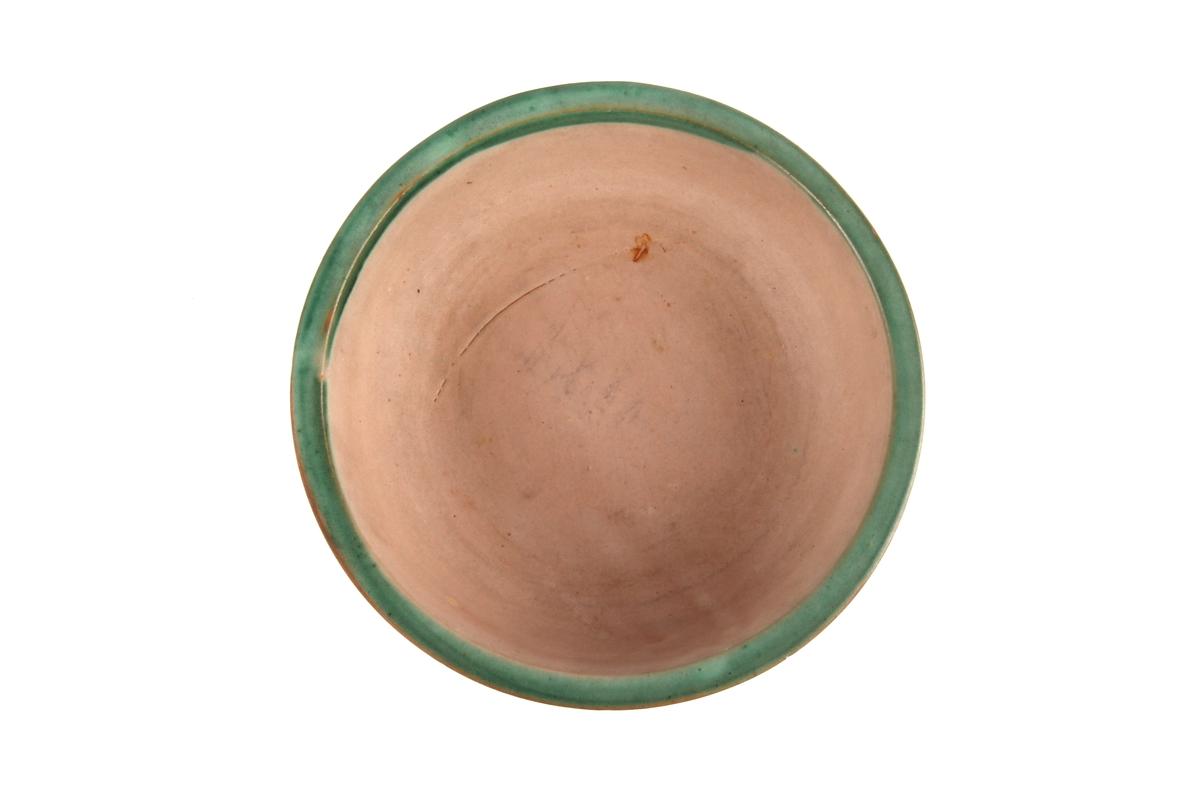 Glasert keramikkskål med grønn kant.