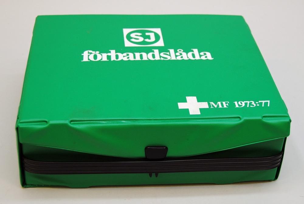 """(Jvm 21605:1) Grön plastlåda med handtag och låsanordning i svart plast. På lådan finns en vit SJ logga och texten """"förbandslåda MF 1973:77"""". Lådan innehåller olika hjälpmedel som till exempel förband, skumplastplatta och värmefilt, samt en instruktionsbroschyr.  (Jvm 21605:2) Röd instruktionsbroschyr med vit text """"Första hjälpen. En handbok om grunderna för första hjälpen vid olycksfall."""". På baksidan står det """"AKLA Sätraängsvägen 8/182 36 Danderyd/Tel. 08-753 02 70."""".  (Jvm 21605:3) Andningsmask i plast som har en påklistrad bruksanvisning.  (Jvm 21605:4) Första hjälpen-filt av aluminiserad plastfolie  (Jvm 21605:5) En fixeringsenhet som innehåller tubnät för fixering av förband, säkerhetsnålar och en mitella.  (Jvm 21605:6) En sårvårdsenhet som innehåller sårvårdskompresser, bomull, plåster, sax, penna och block.  (Jvm 21605:7-8) Två stycken katastrofenheter som innehåller förband i tre storlekar och en elastisk binda."""