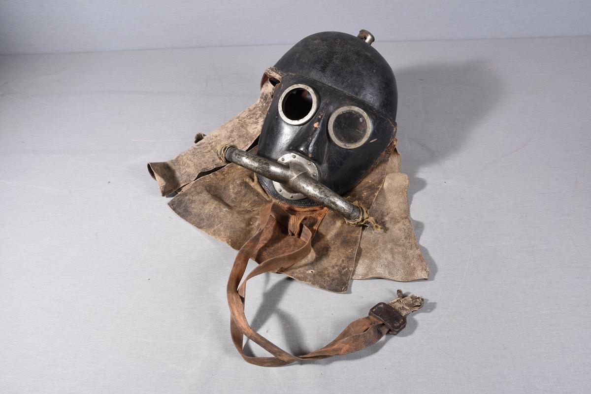 Hjelm for røykdykking, med sirkelrunde glass for utsyn. Formstøpt utsparing for nesen. Over munnen metallfeste for slanger på hver side. Skinnbeskyttelse på nedre del av hjelmen.