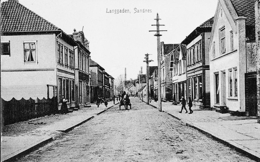Langgata på Sandnes sett frå sør mot nord. Andre hus på venstre side er Sandnes Forbruksforening, deretter E. P. Aase, O. Sæland, og K. Sivertsen. Første hus på høgre sida er slakter Racin Nygaard.