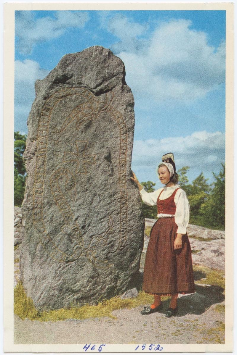 """Vykort med motiv från Skansen. """"Dräkt från Häverö, Uppland."""" Kvinna i folkdräkt invind runsten, """"Norslundastenen""""."""