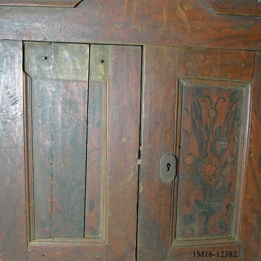 """Väggskåp, häng i ek. Stomme sinkad ihop. Upptill svängt, profilerat krön, nedtill liknande. Massiva dörrar, utformade för att likna """"ram med fyllning"""". Invändigt två hyllplan i furu, även bakstycket är i furu. Skåpet är ådringsmålat i röd-brunt med blomstermålning på dörrarnas fyllningar. Initialerna AIS är målat på krönet. Nyckelhålsbeslag, låskista och gångärn i järn. Inköpspris 3 kr."""