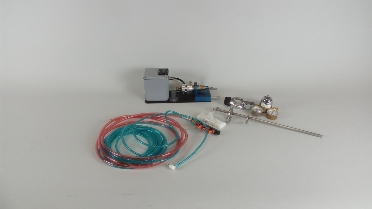Injeksjonsmaskin/pistol. Brukt til å vaksinere opprettsfisk. Dette er en luft-betjent maskin/pistol spesielt designet for effektiv vaksinasjon av levende fisk.  Består av telleverk (Carlon) og injeksjonsenhet hvor man kan monteres en kanyle.  Plastslanger, stativ og koplingsenheter. Trykkluftventil og kanyler (2 stk).