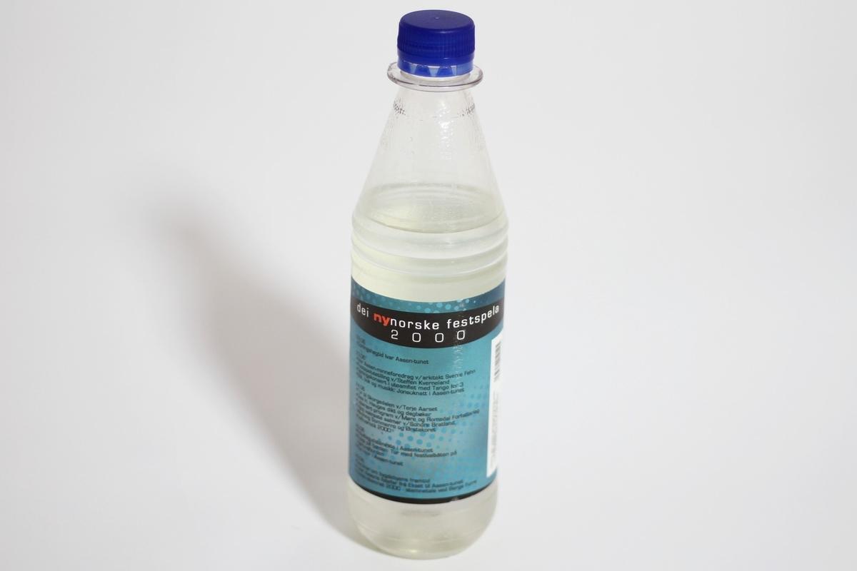 """Gjennomsiktig plastflaske for mineralvatn med avrunda sylinderform i nedre del og kjegleform i øvre del. Det er ein blå skrukork i plast over den sylinderforma drikkeopninga. Etikettane er hovudsakleg blå og svarte, og er designa av festspelkunstnaren Steffen Kverneland. Øvre del av den fremre etiketten viser fem karikerte andlet av kjende personar. Under dette står tittelen """"festspelbrus dei nynorske festspela 2000"""", tidsomfang for festspela og namn på produsent og kunstnar. På den bakre etiketten er ei topplinje med innskrifta """"dei nynorske festspela 2000"""", og under ei detaljert programoversikt for festspela."""
