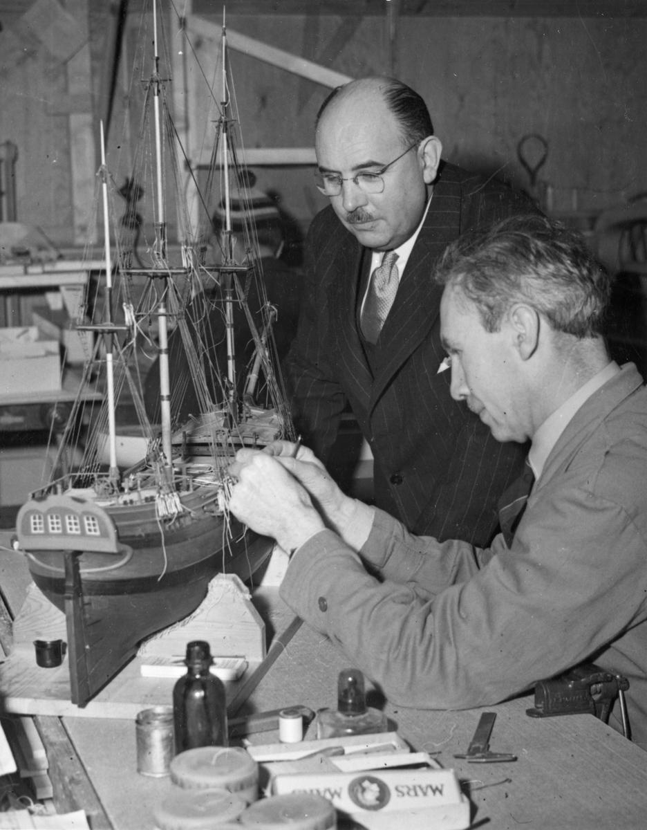 Sjöhistoriska museets modellverkstad. Modellbyggare Harald Åkerlund i arbete med en modell av kattskeppet BARON ANDERS von HÖPKEN. I mitten museidirektör Gerhard Albe.