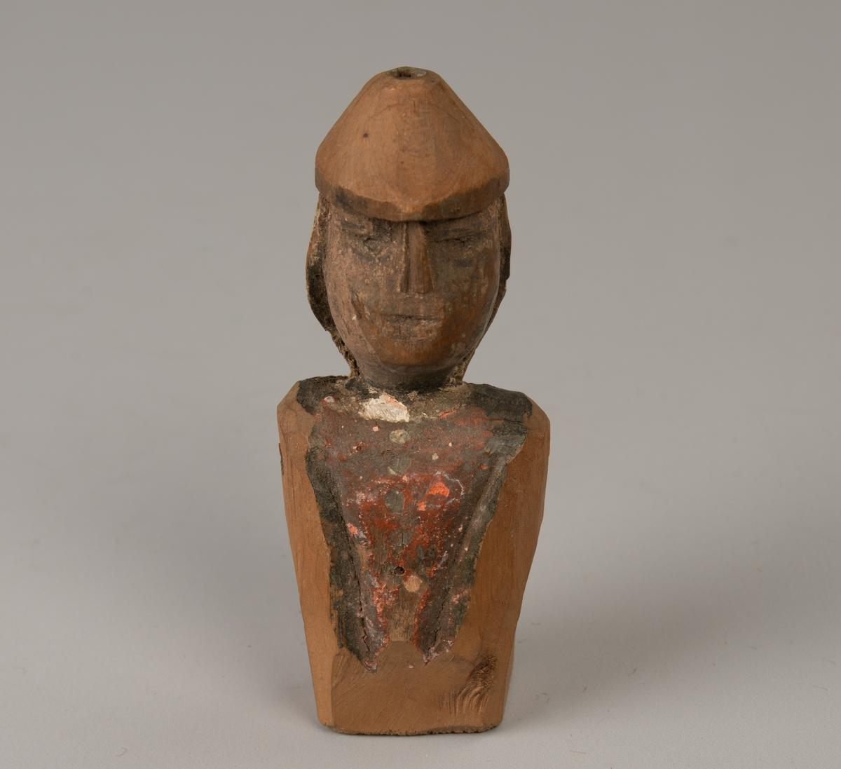 """Ovalt hode med rett nese helt opp til den pyramideformede hatt,  hull i toppen.  Smale øyne, rett munn, skjev i forhold til nesen. Mørkt ansikt og skuldre og  trekantet stykke på forkroppen. Skuldre og nedre del er umalt,  med rektangulær bunnflate. Over bakhodet hvitt """"hår"""" eller tekstil."""