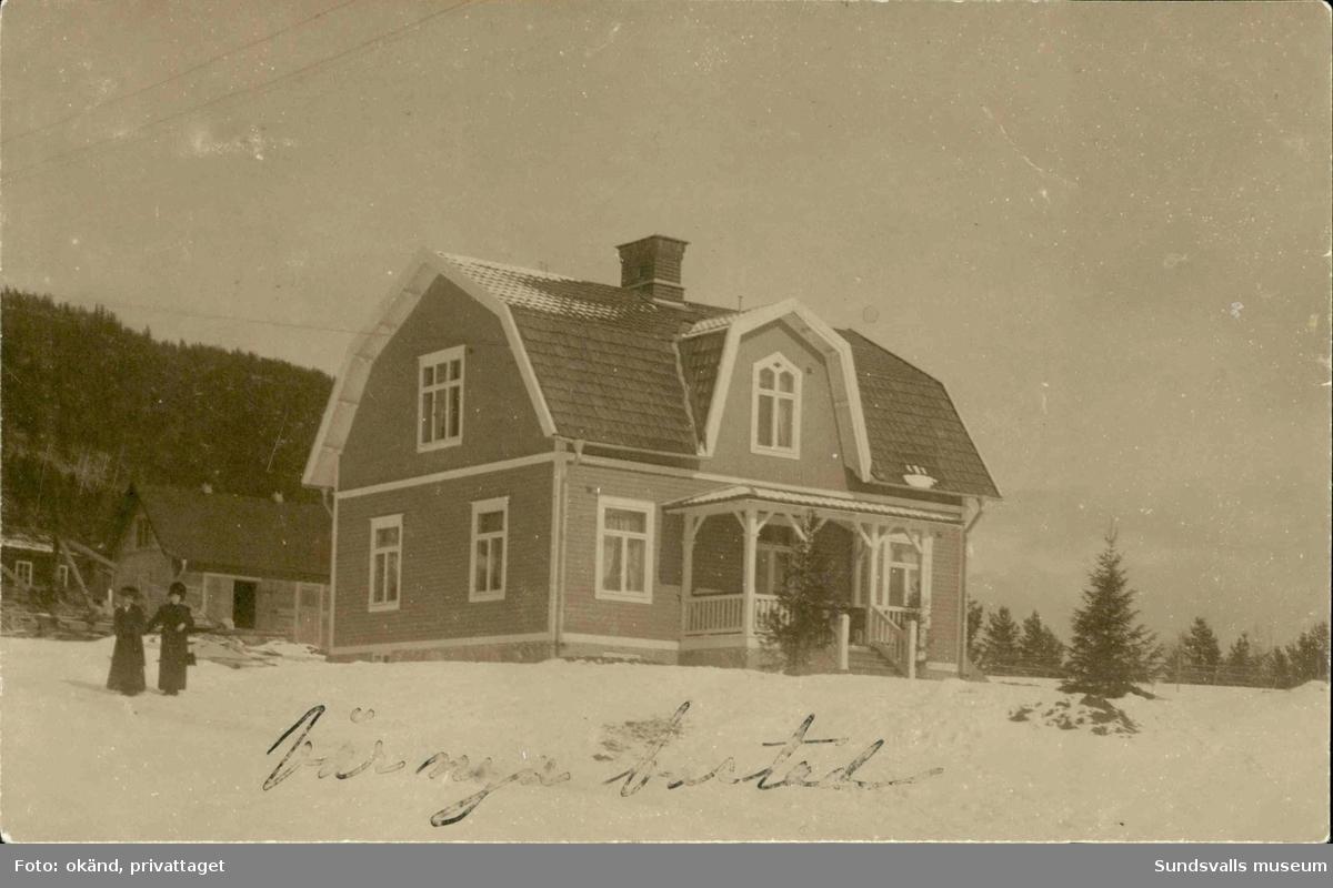 Vykort med vintermotiv av ett par kvinnor stående utanför ett bostadshus i Johannisberg.