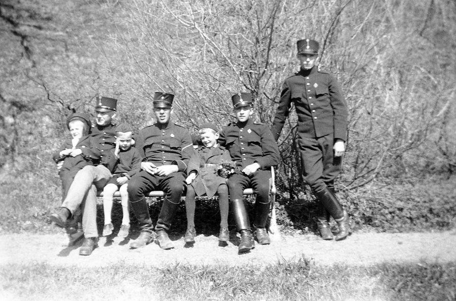Furir och tre värnpliktiga i uniform m/ä. Tre cilvila ynglingar.