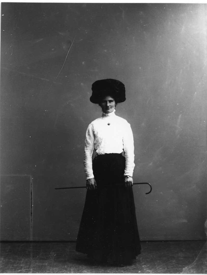 Porträtt av Hilma Hammagren. Hon står med mörk lång kjol och ljus blus. Hög hatt på huvudet håller en smal käpp vågrätt med båda händerna.