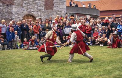 To riddere i rustning og med røde overkapper utkjemper blankvåpenkamp foran Storhamarlåven. Mellom ridderne og låven er det en stor menneskemengde som ser på kampen.. Foto/Photo