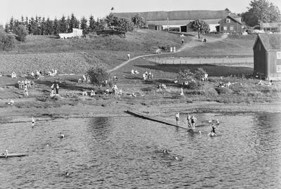 Svart-hvitt fotografi som viser mange mennesker som bader og soler seg. Det er gress på bakken og en lang brygge utover i vannet. I bakgrunnen vises Storhamarlåven.. Foto/Photo
