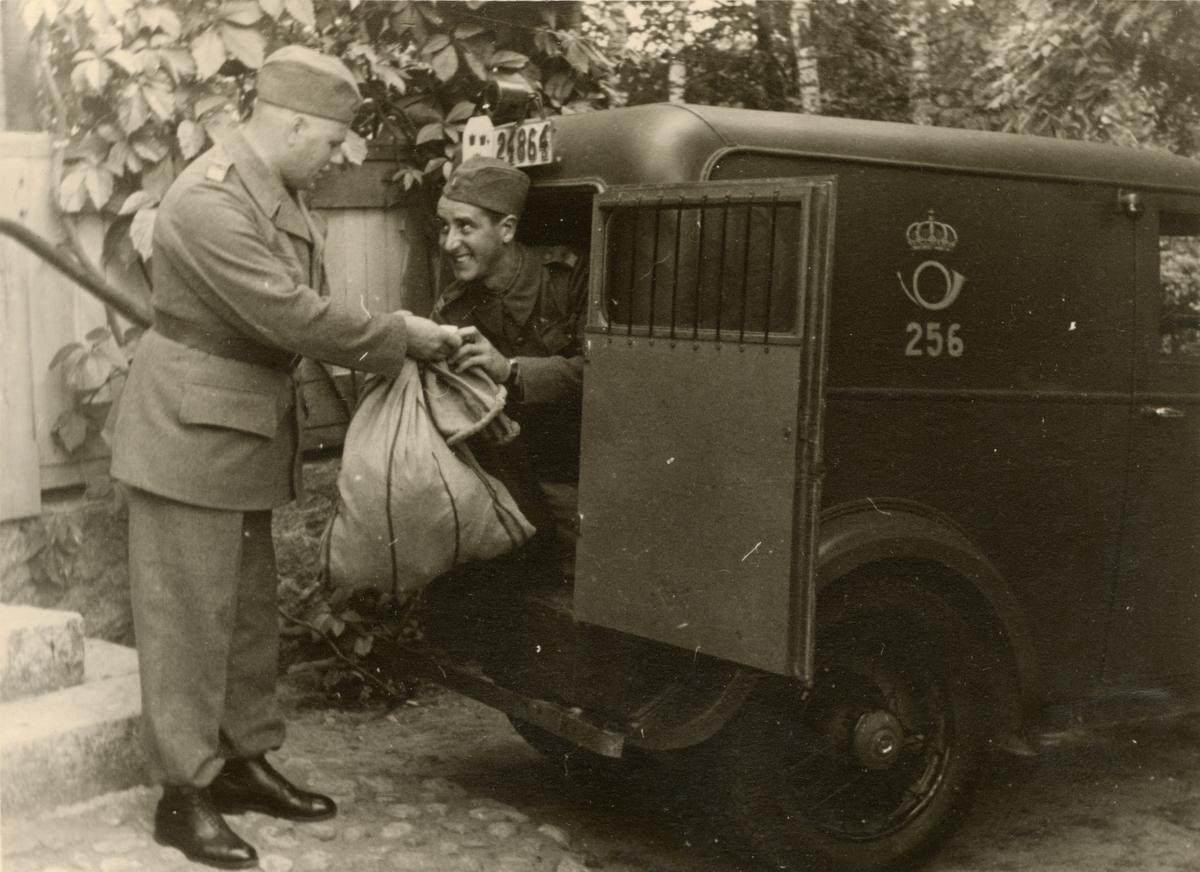 """Text i fotoalbum: """"Beredskapstjänst april-okt 1940 vid Fältpost"""". Två män vid postbil."""