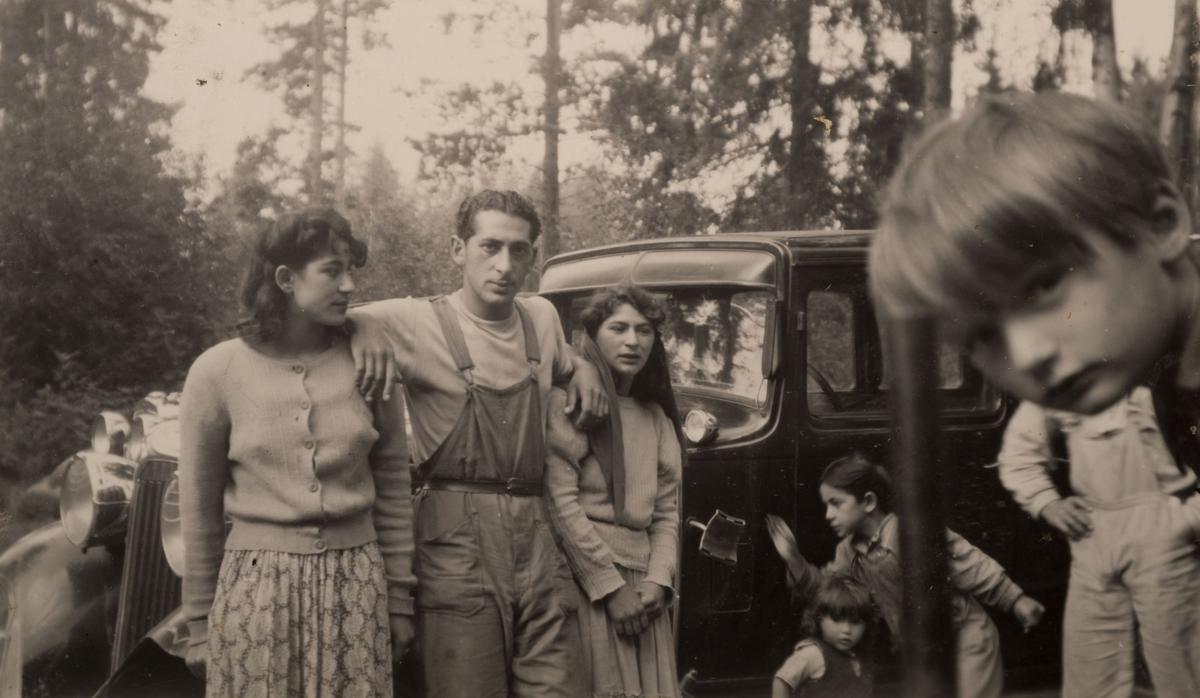 Familjen samlad för fotografering vid bilen. Ett barn kikar fram och skymmer en del av motivet. I bakgrunden syns barrskog. Bilden är tagen i juli 1950 i Storvik.