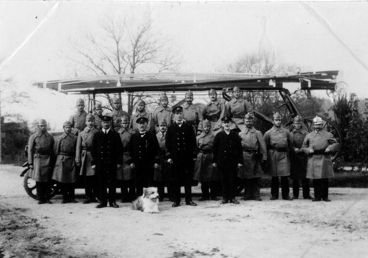Alingsås brandkår uppställda framför brandbil med stege. Framför dem ligger en hund.  Översta raden från vänster:  Albin Lindberg (plåtslagare), Albin Lindohf (sotarmästare), Oscar Söderberg (skomakare), Carl Andersson (snickare), Carl Johansson (målare), Carl Björklund (skolvaktmästare), Konrad Kihlander (målare), Oscar Lind (badmästare).  Mellersta raden från vänster:  Harald Karlborg (mekaniker), Artur Peterson (målarmästare), John Svedberg (f.d. snickare), Harry Andersson (sadelmakare), Fridolf Andersson (möbelsnickare hos Kopp), Harry Peterson (målarmästare), Claes Matsson (gasverksarbetare), John Blomqvist (kusk vid brandkåren), Tor Björkman (målare), L.M. Sandin (gasmästare).   Främre raden från vänster:  Fridolf Hallgren (brandmästare), John Möller (brandchef), Anders Hedén (vice brandchef), Carl Söderholm (brandförman).