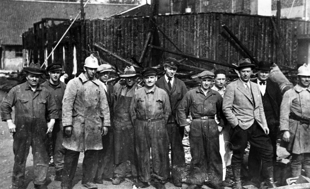 Branden hos Nordiska Suchard natten till den 8 maj 1935. Ett antal män uppställda framför det nedbrunna huset.