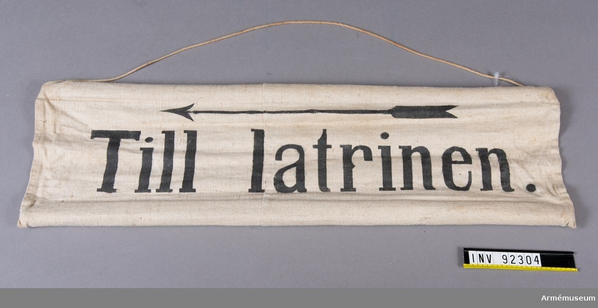 Skylt av tyg med träpinnar i sydda kanaler på långsidorna. Upphängningssnöre. Svart text: Till Latrinen