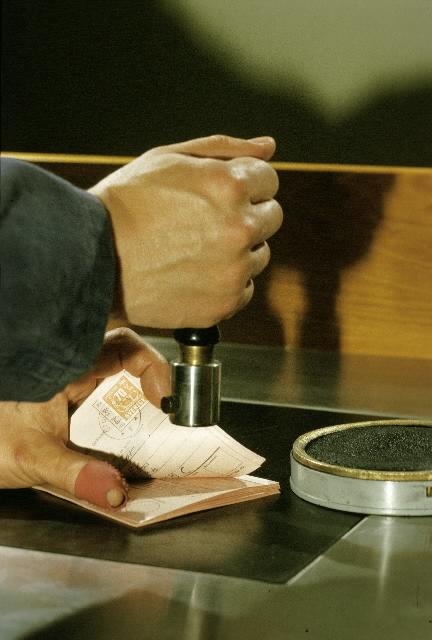 En postiljon - i en arrangera situation - ankomststämplar bl a baksidan av pa-ketadresskort. Bilden är tagen på ett stämpelbord i moderna postkontoret i Postmuseum.
