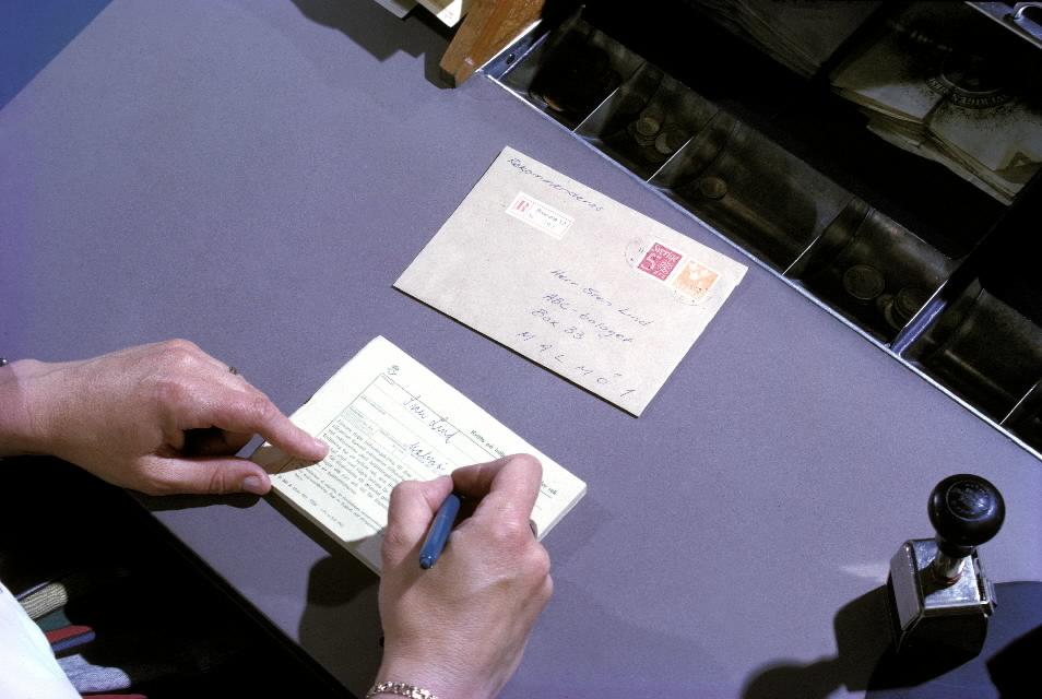 Seriebild H 7. En postkassör på poststationen Bromma 12 skriver ut ett kvitto på inlämnat rekommenderat brev, som är frankerat ochförsett med en rek-etikett. T h står en stativstämpel.